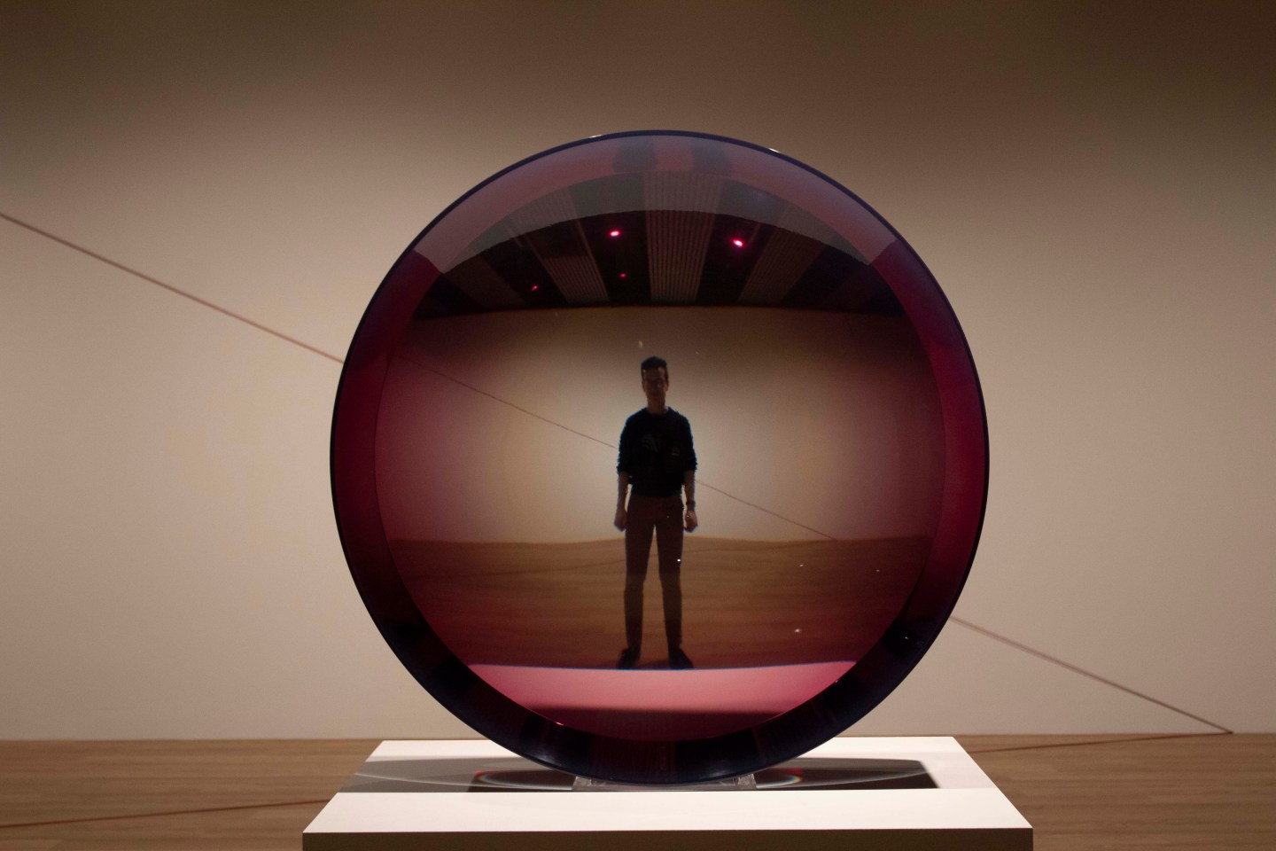 Man stands behind concave purple glass giving the illusion of being very far away