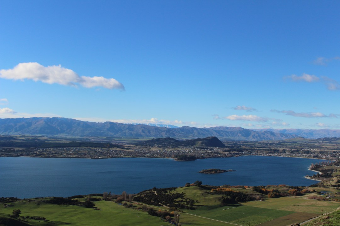 views over Lake Wanaka and the town with blue skies and mountains in the distance