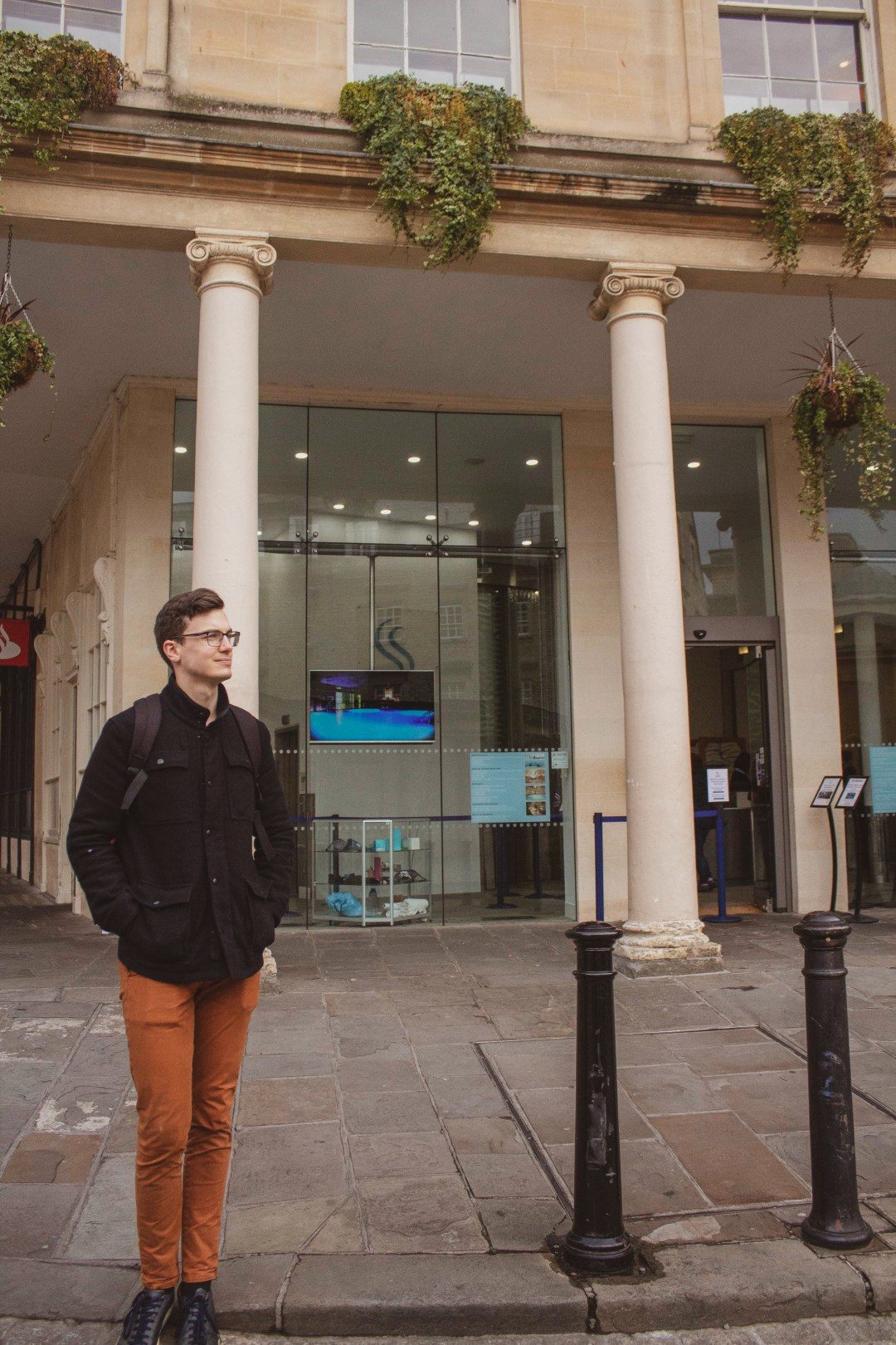 Man stands outside building in Bath looking into the distance