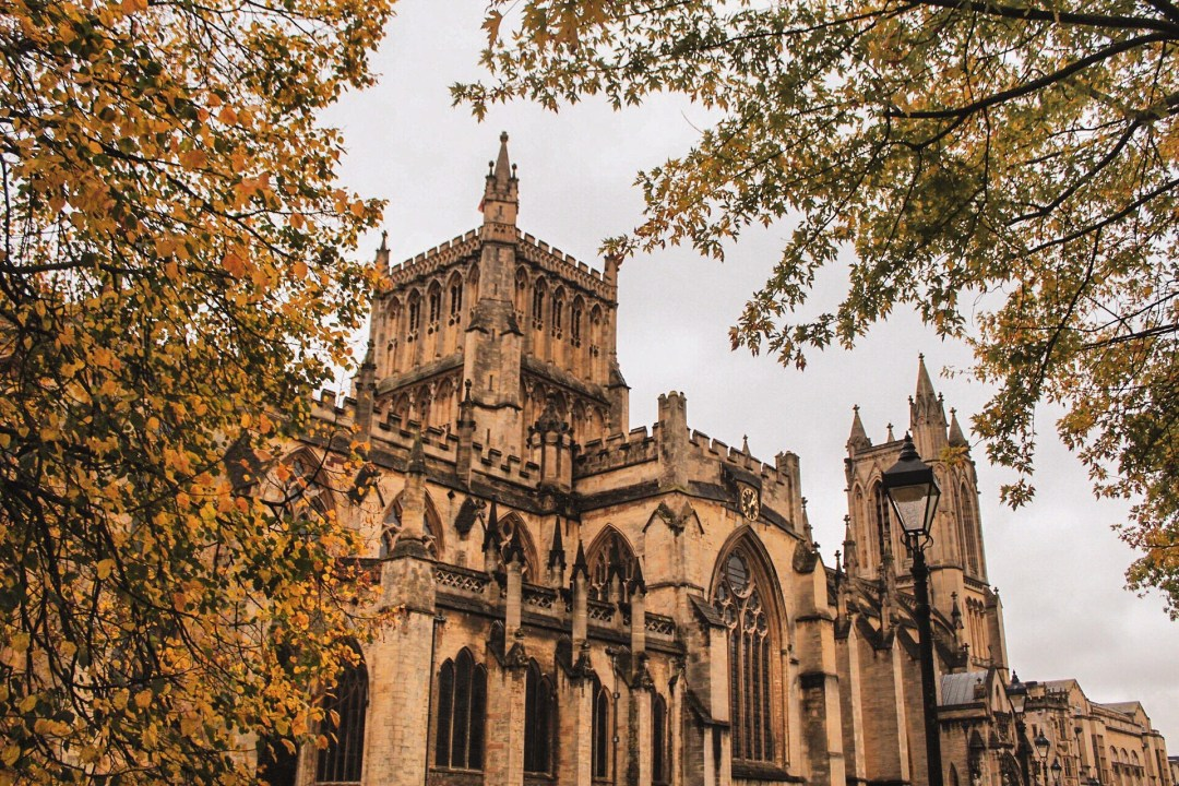 Visit Bristol In One Day Trip - Explore Bristol's harbourside, famous landmarks, and beautiful countryside for an immersive taste of history, world exploration, and engineering! Golden autumn leaves perfectly frame Bristol Cathedral.