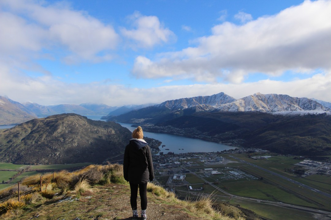 Girl looks over lakes and snowcapped mountains in New Zealand