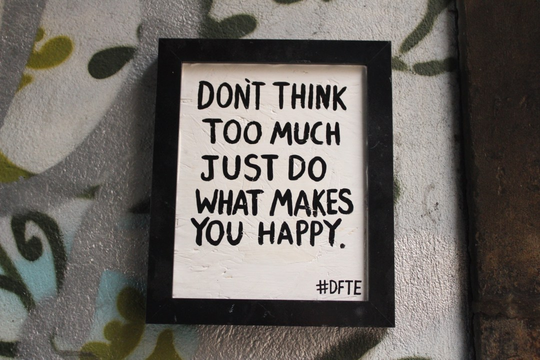 "Street art reads: ""don't think too much just do what makes you happy"" in Bristol"