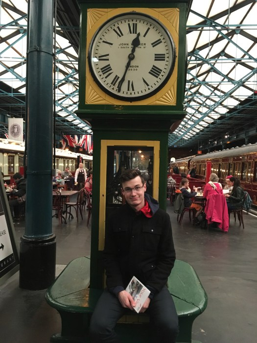 Man sits below clock at a station museum