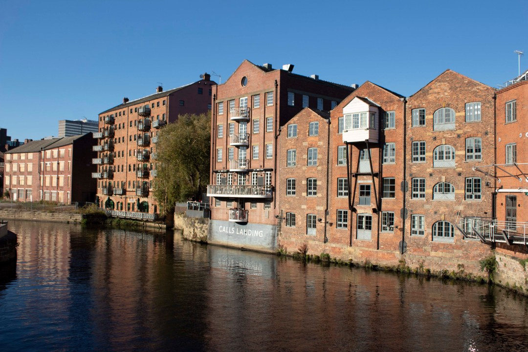 Historic buildings sit on the edge of a river