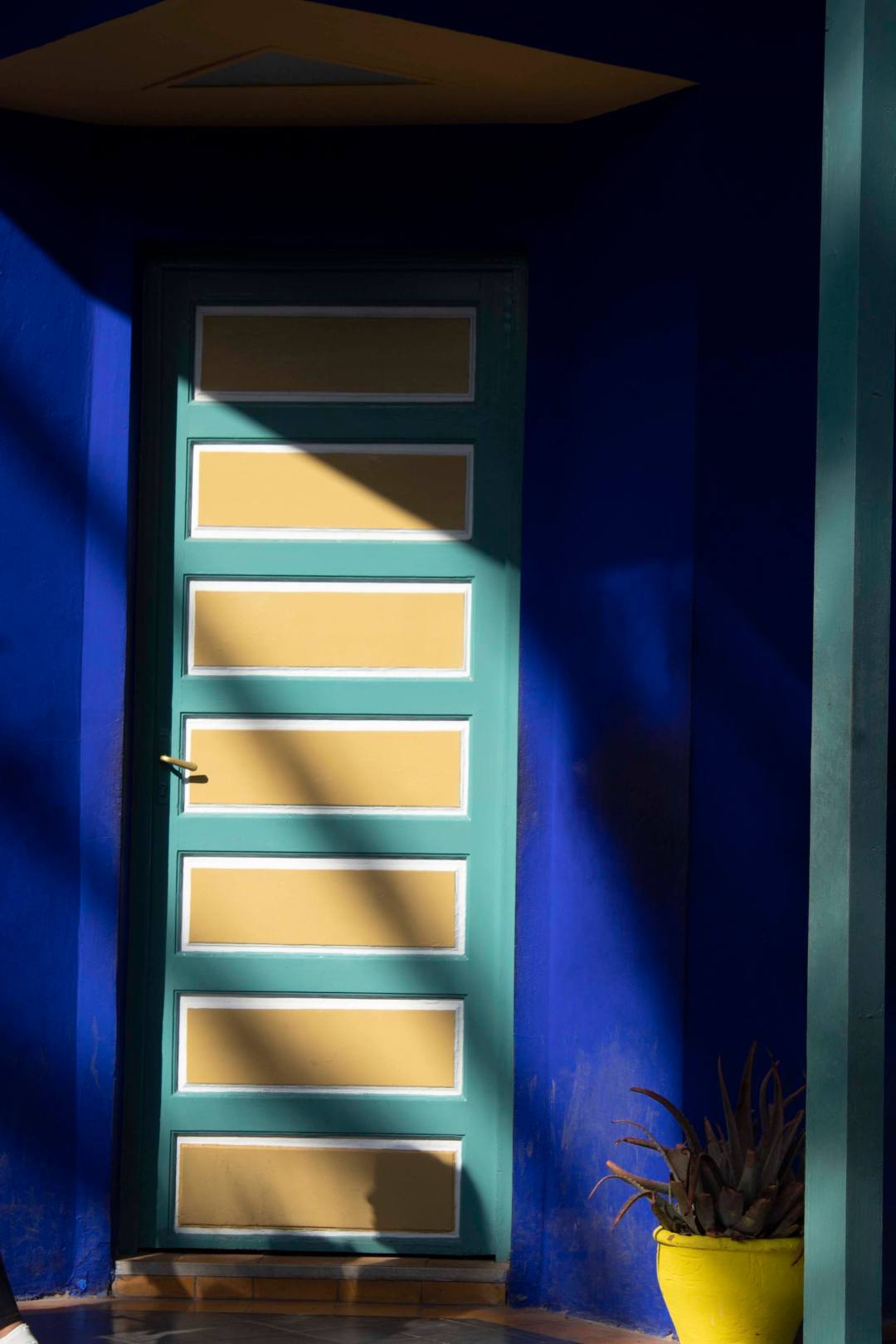 yellow and green door against blue wall with streaks of sunlight