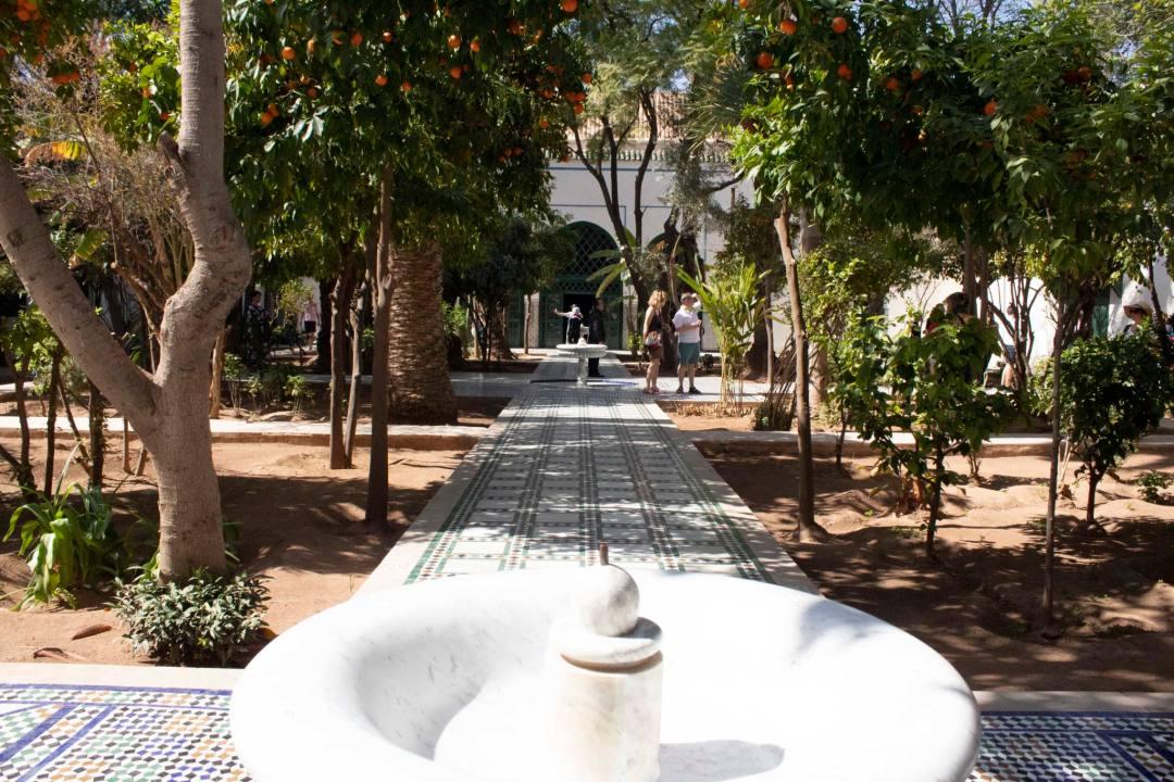 white fountain and tiled path through marrakech garden