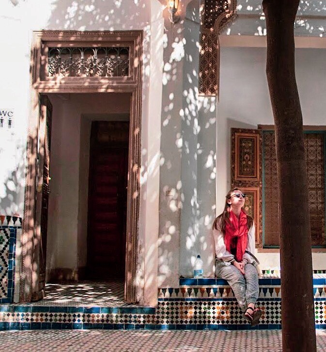 woman sits in Bahia Palace marrakech looking up to sky