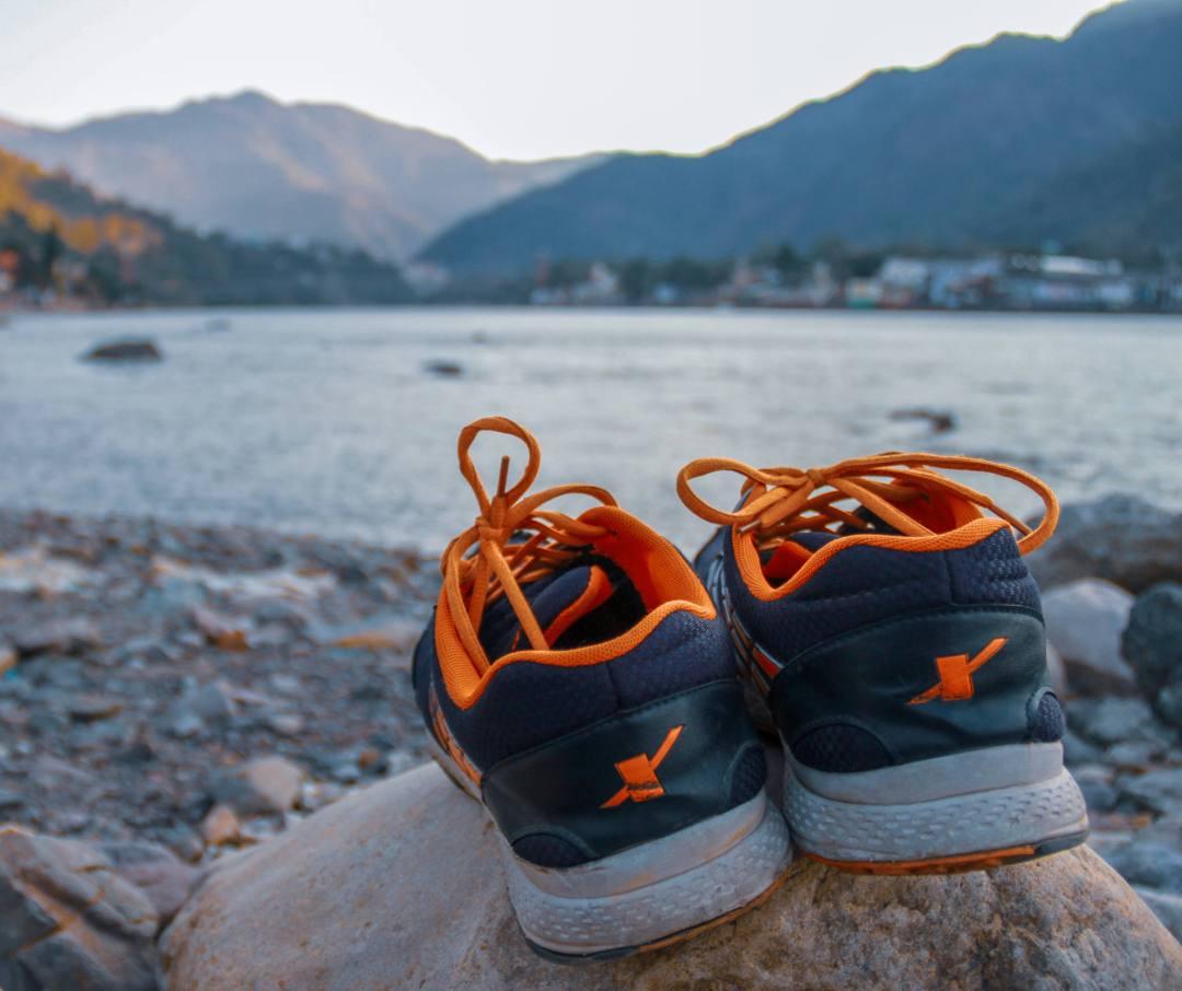 trekking shoes sit on rock overlooking lake
