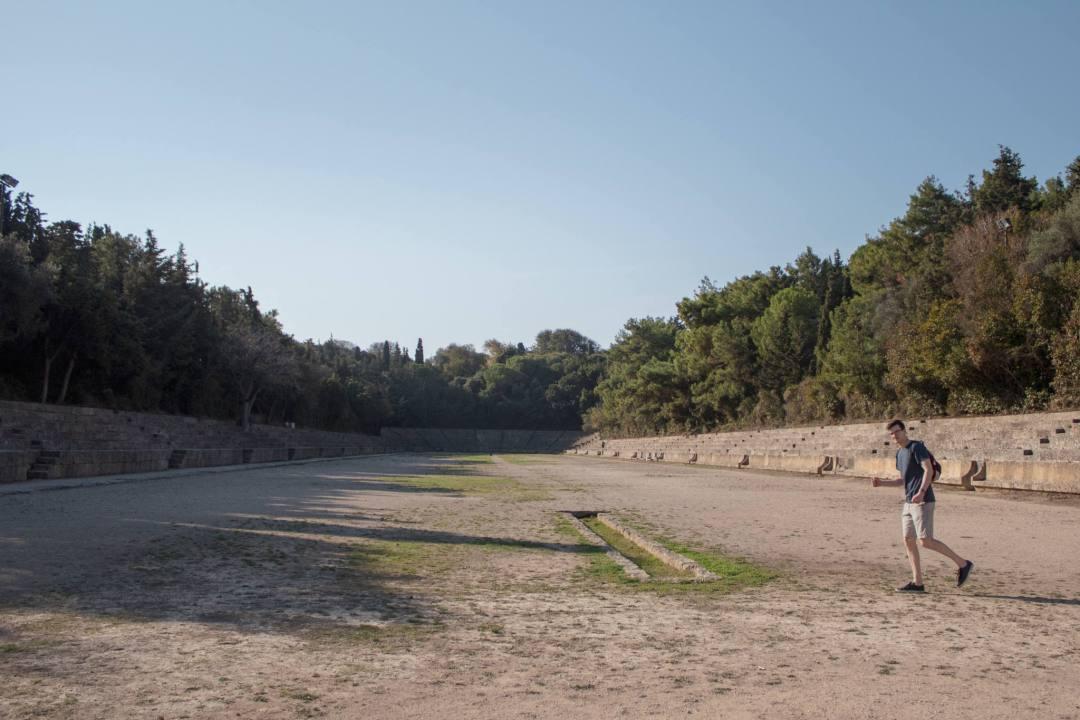 Man pretending to run in stadium ruin at Acropolis of Rhodes