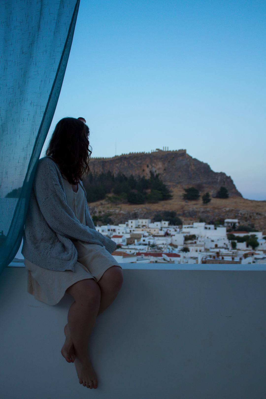 Woman looks out across Lindos village to acropolis from balcony