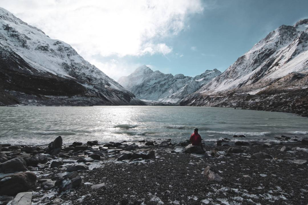 man sits on rock in front of glacial lake in aoraki/mount cook national park
