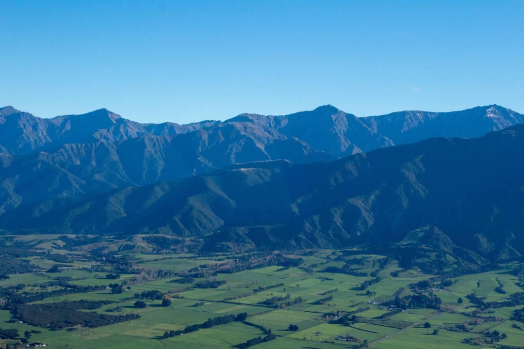 green fields besides mountains