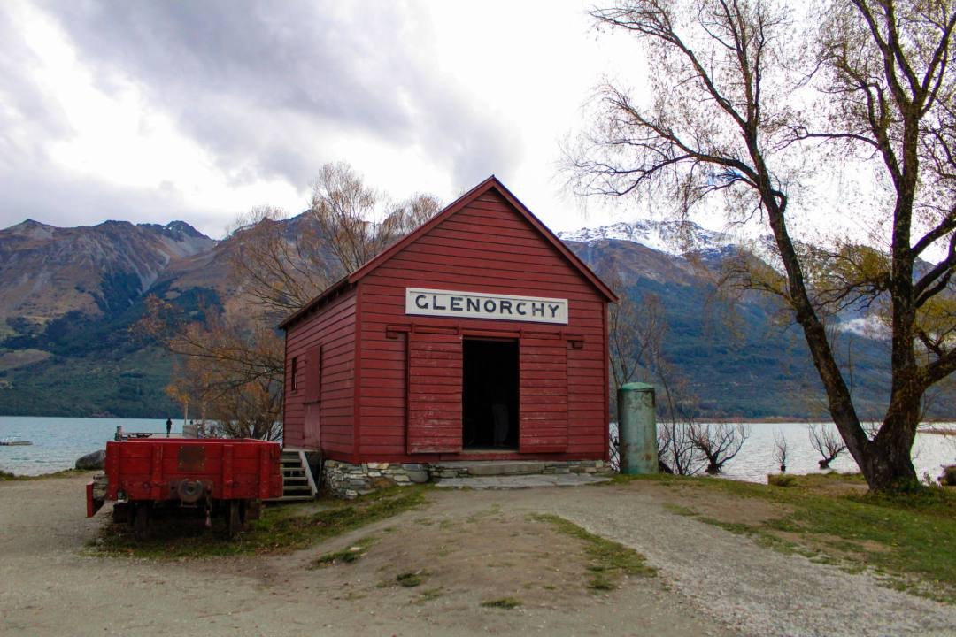red boat shed in front of lake and mountains