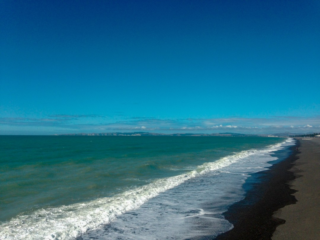 black sand beach and waves on sunny day