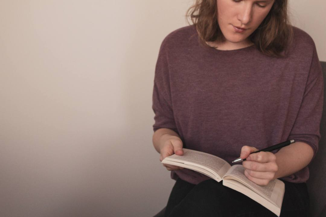 woman reads book holding pen