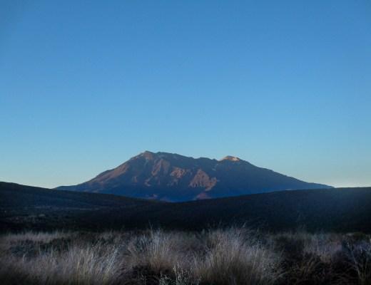 Mountain at sunrise overlooking grassy plains