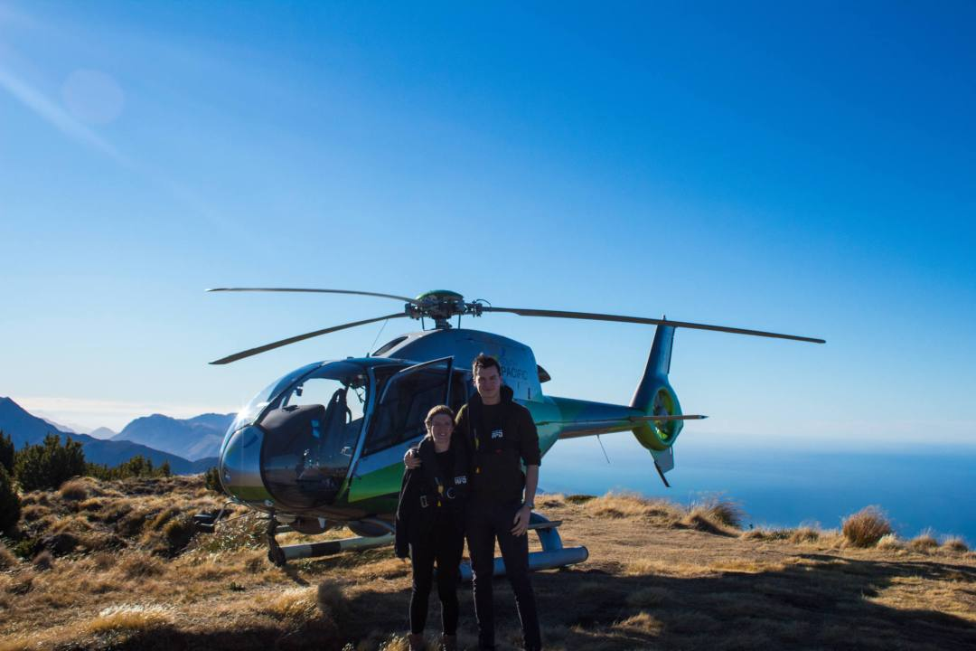 two people standing in front of helicopter on mountain top