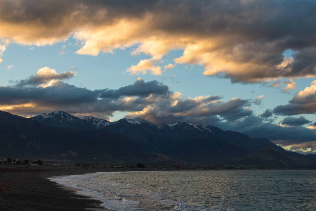sunset over mountains and beach in kaikoura