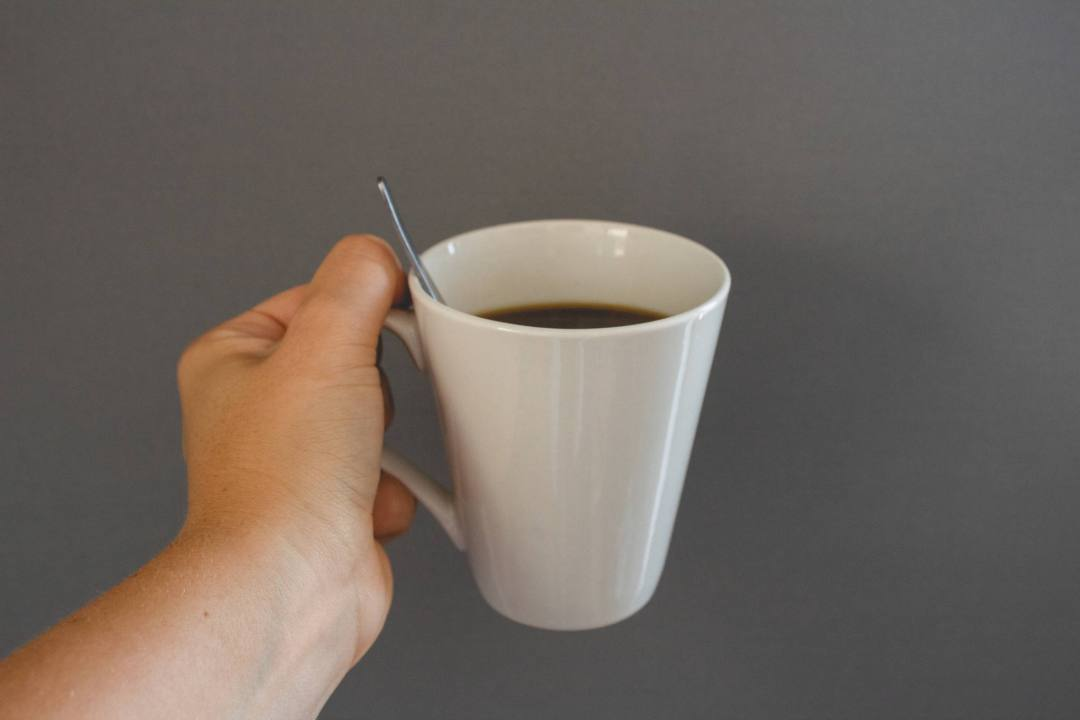 hand holding mug of coffee