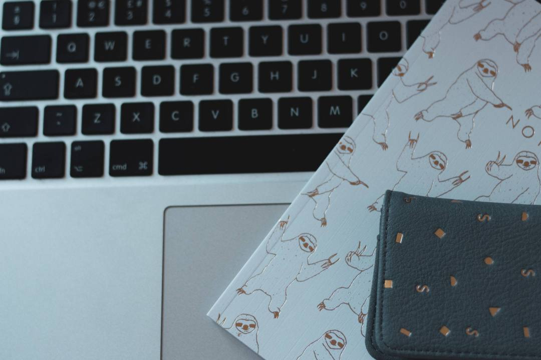 purse and notepad on laptop keys