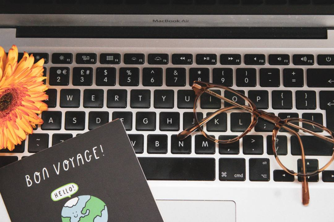 laptop with glasses, flower, and card
