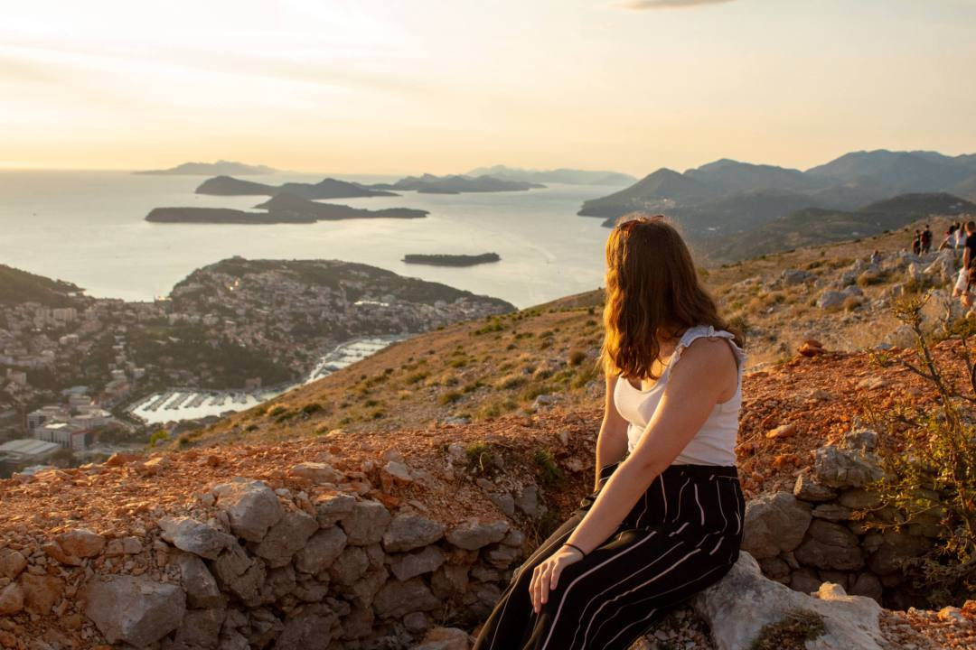 woman looks over dubrovnik and islands from mount srd