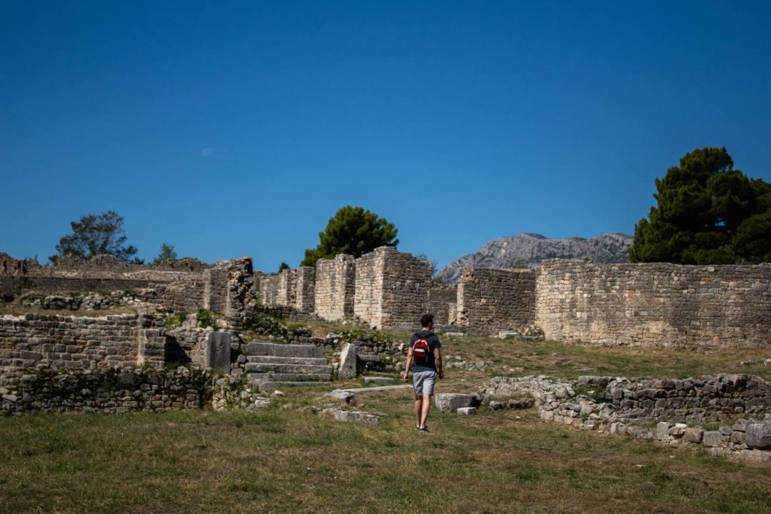 man walks through roman ruins