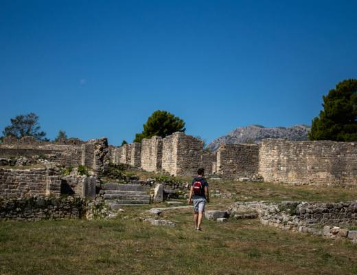 man walks through roman ruins