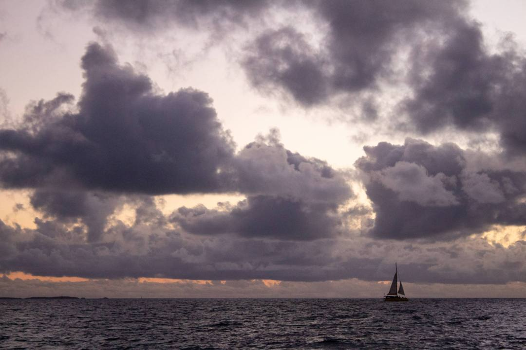 sailboat at sea during cloudy sunset