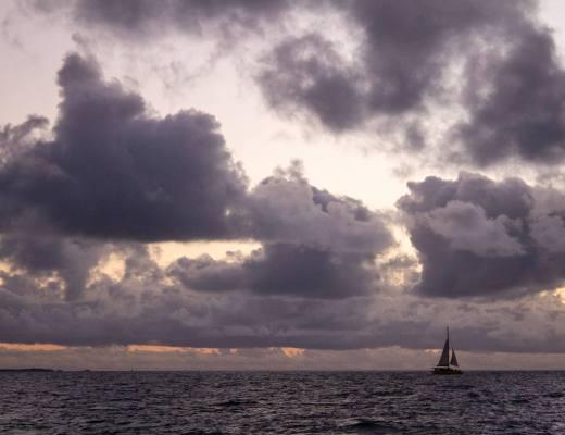 sailboat at sea during cloudy sunset