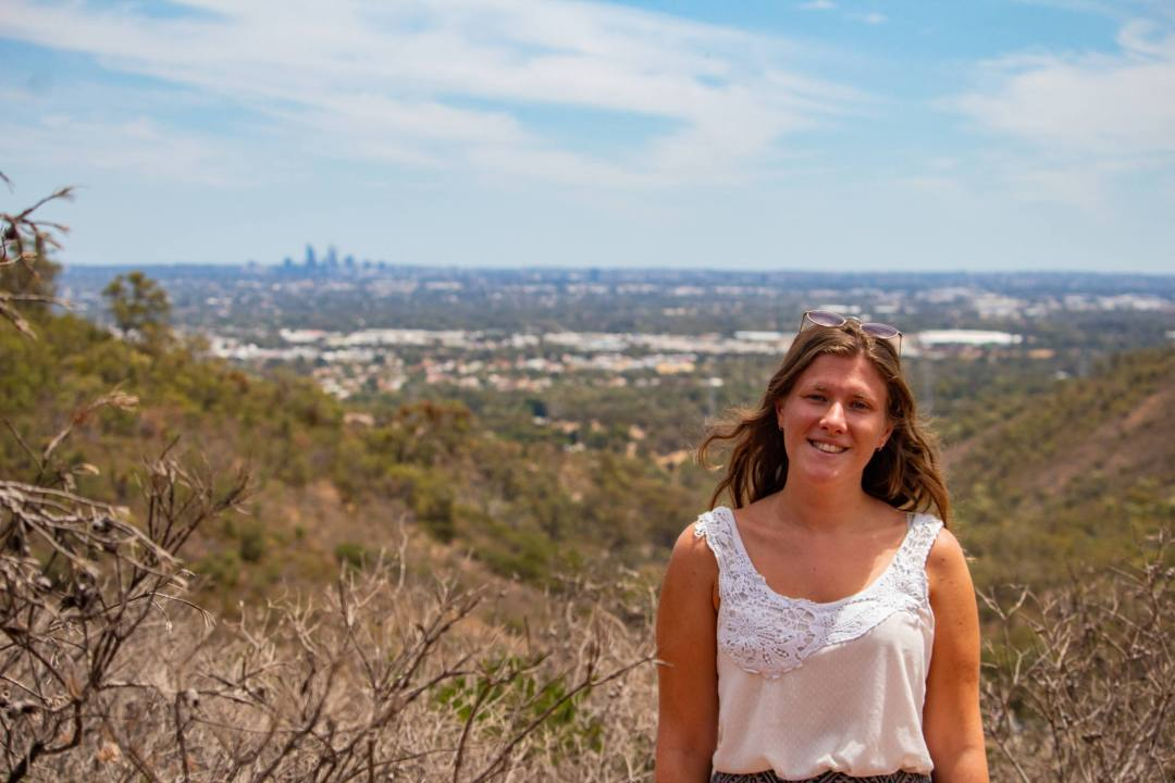 woman smiles atop viewpoint overlooking nature reserve and perth city