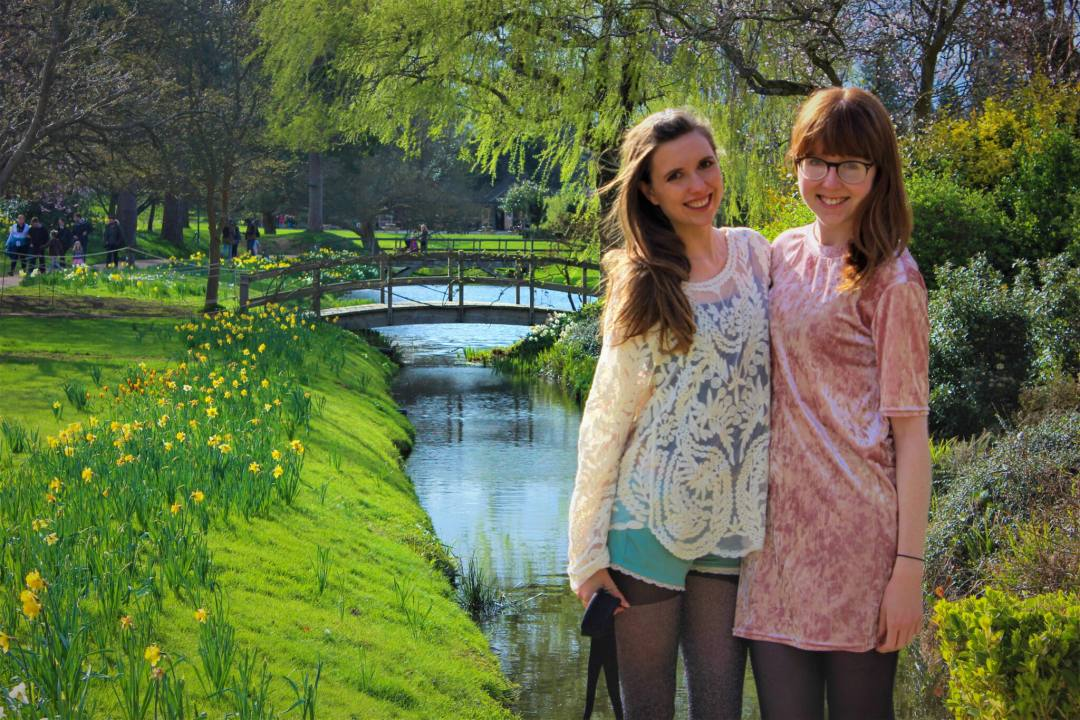 Friends smile at camera standing in Hever Castle gardens and moat in springtime