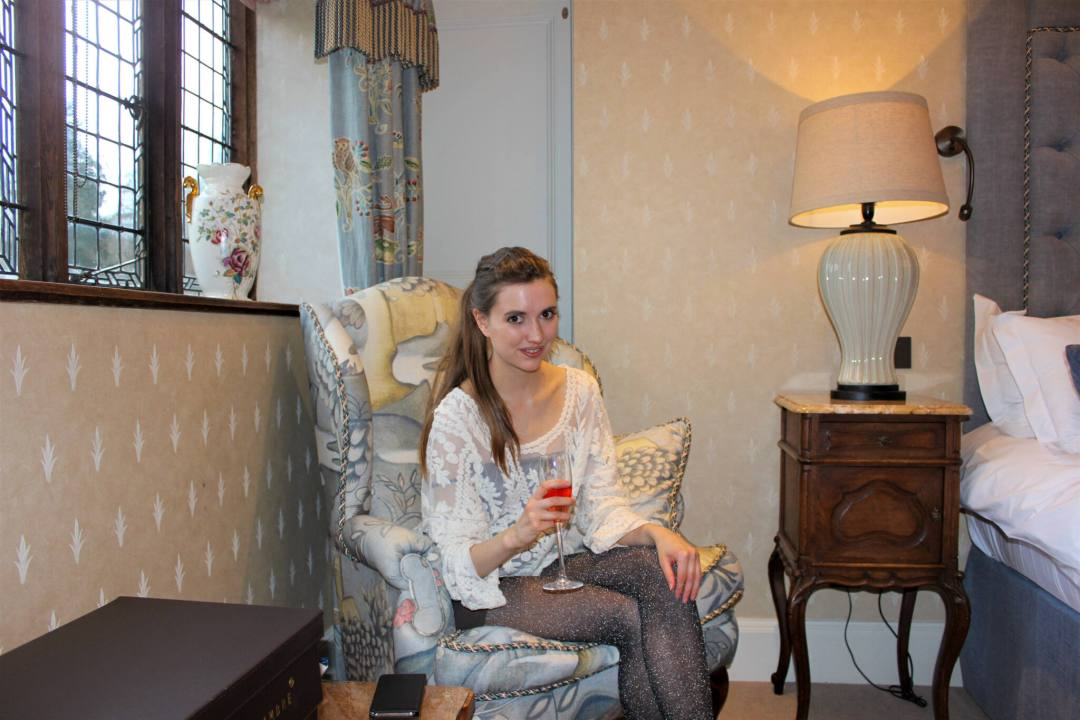 woman sits in luxurious hotel room chair at Hever Castle