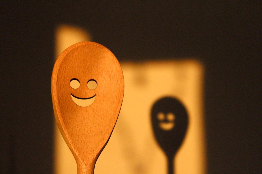 a wooden spoon with smiley face cut out is close to the camera with its shadow reflected on the wall behind