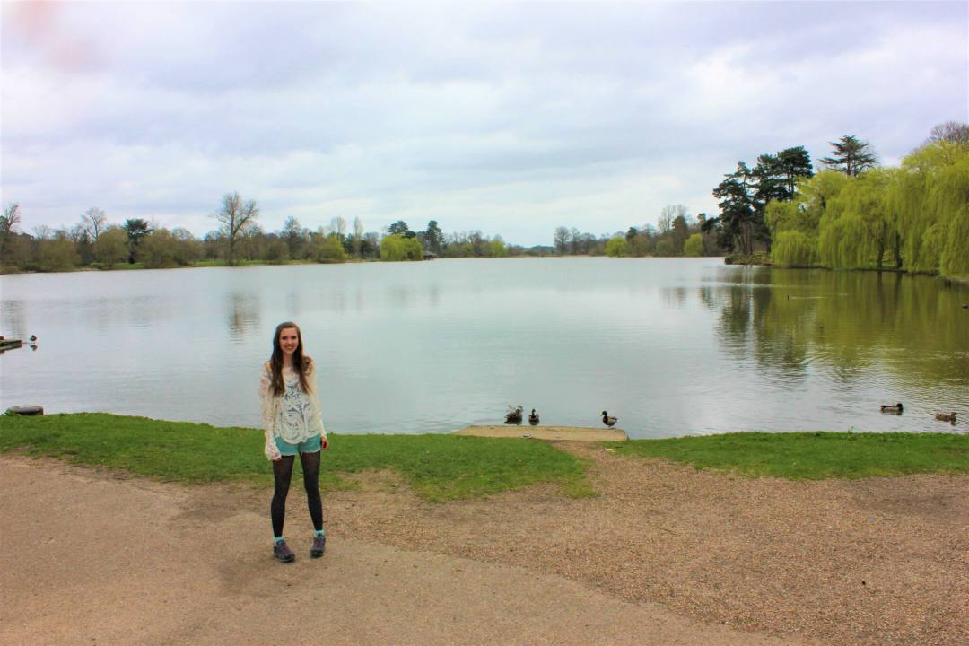 woman smiles at camera in front of Hever Castle lake