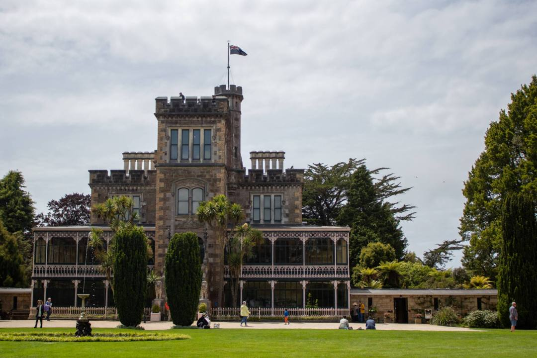 Front facing view of Larnach Castle with period style features and terraces of a brickwork building