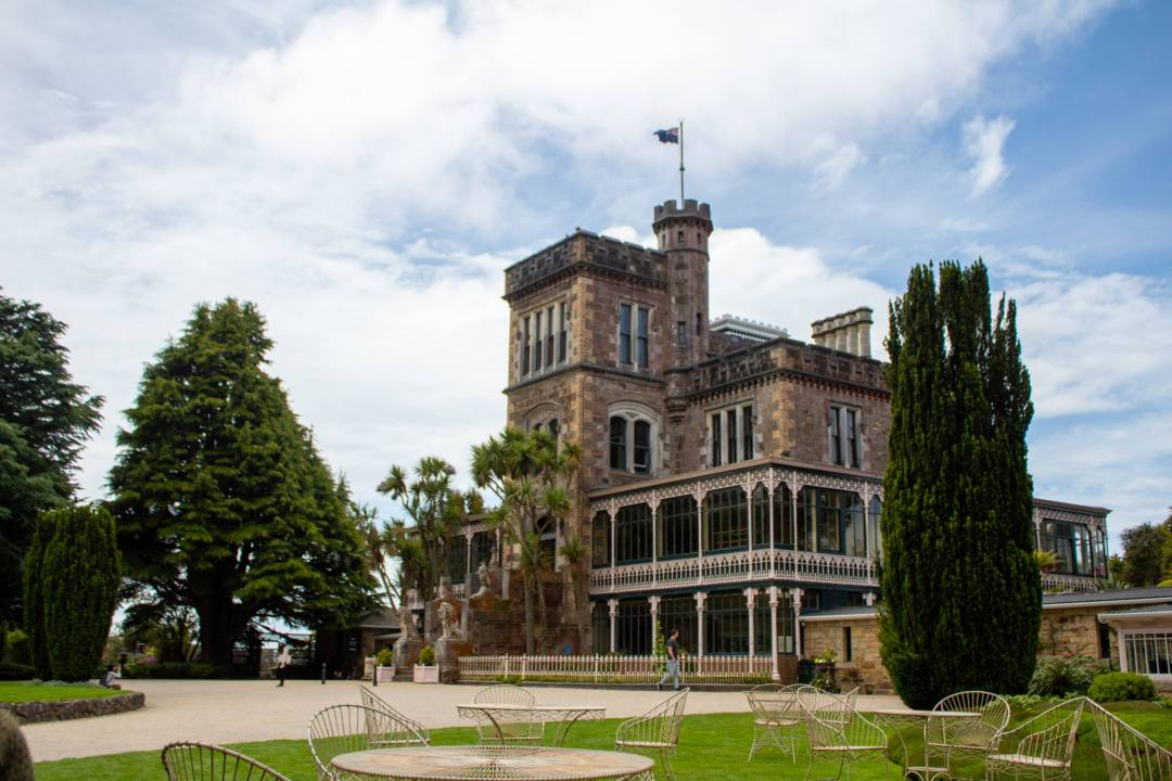 Front view of Larnach Castle surrounded by trees and outdoor seating