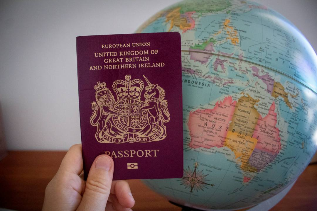 Hand holds a British passport in front of a globe which shows a map of Australia
