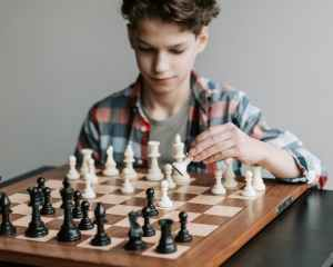 boy in red and white plaid button up shirt playing chess