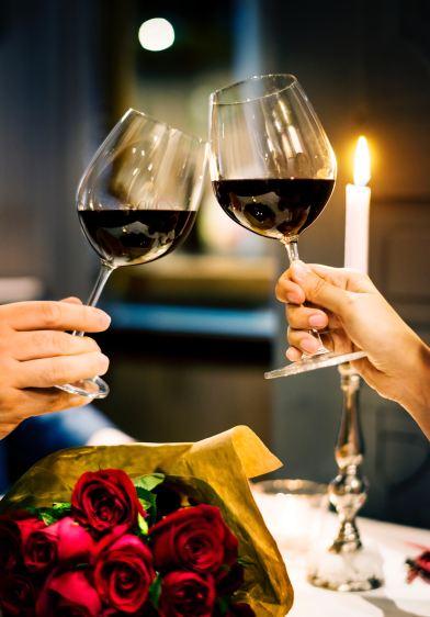 dve sklenice cerveneho vina ruze a svicka