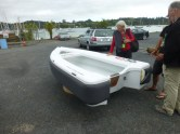 A guy in Opua is trying to come up with a light weight fiberglass dinghy that is easy to take care of. This one weighs 85 pounds and has Sunbrella covered floating foam on the exterior, So even with a 15 hp motor it still floats pretty high, rows good and carries 4 people, can stand up to coral and sand abuse, plus padding for bumping up against your boat.