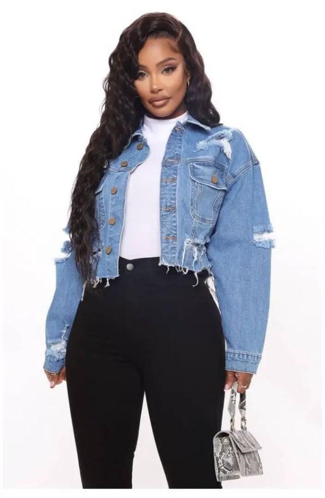 lady layering jean jacket on white turtleneck top