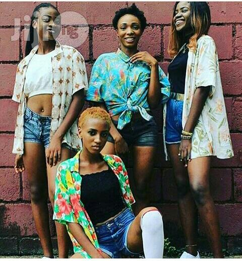 4 ladies layering vintage shirts on crop tops and jean shorts