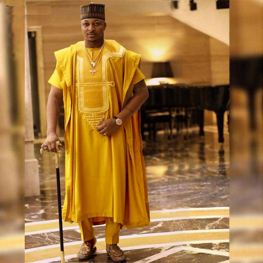 man rocking orange agbada with cap and a cane