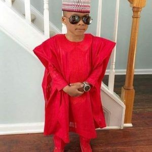 a kid rocking a red agbada with a cap and sunglasses