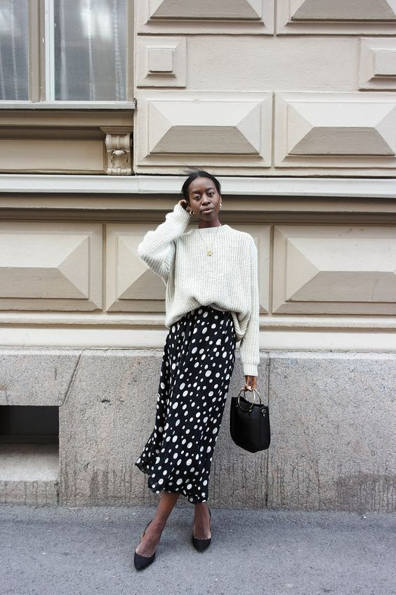 white sweater on a black and white polka midi skirt