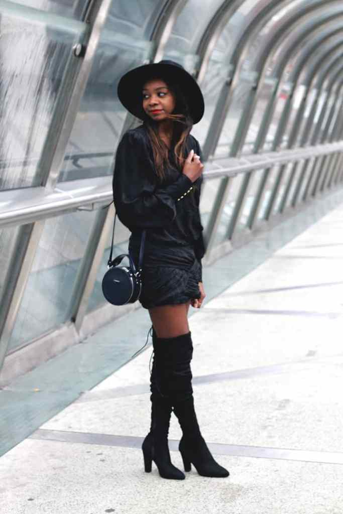 lady in all-black rocking a black over-the-knee boots with heels