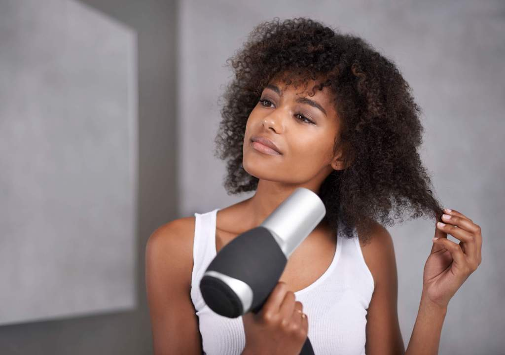Pretty lady blow-drying her hair
