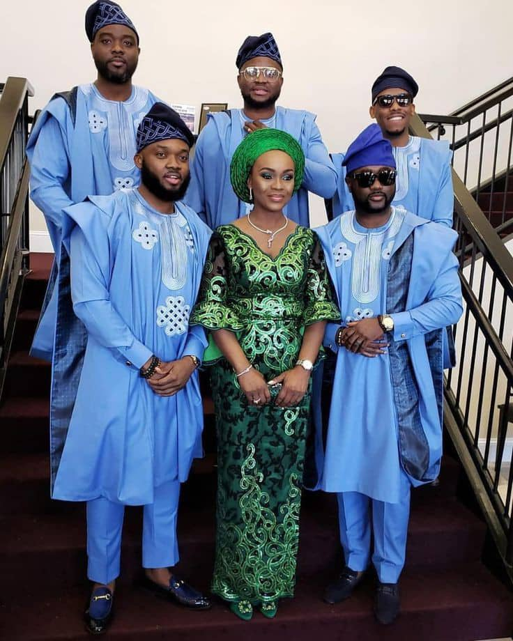 lady standind with men wearing agbada