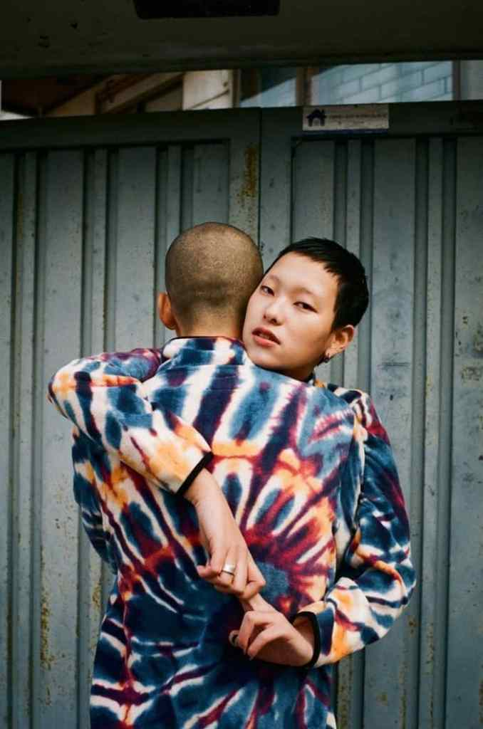 couple in matching adire attire hugging